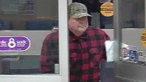 L'image est un peu brouillée. On y voit un homme sortir d'une banque.