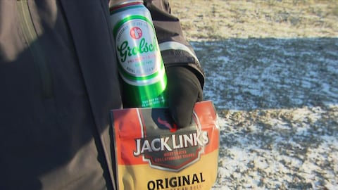 Une canette de bière et un sac de boeuf séché