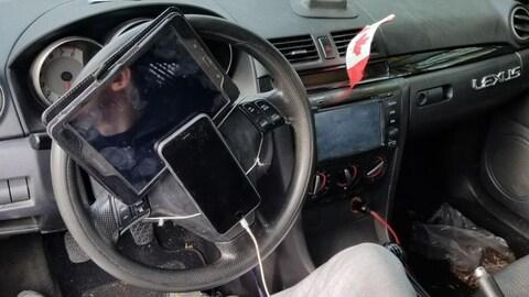 Intérieur d'une voiture dans laquelle un téléphone cellulaire et une tablette numérique sont attachés sur le volant.  Des écouteurs sont branchés dans le téléphone.