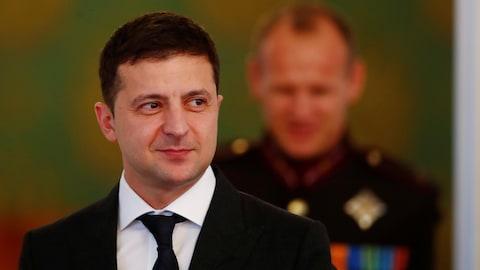 Volodymyr Zelensky a les yeux qui scrutent à droite.