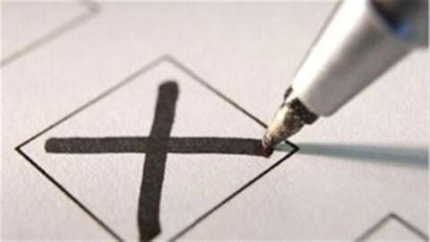 Un crayon trace un X sur un bulletin de vote.