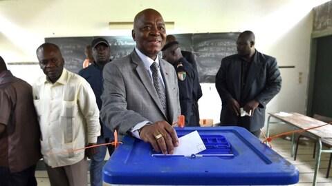 Un homme politique en costume dépose son bulletin dans une urne en plastique, recouverte d'un couvercle bleu.