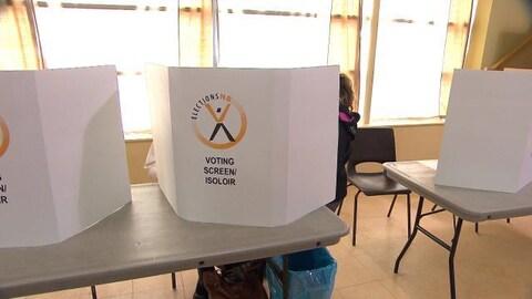 Des personnes remplissent leur bulletin de vote