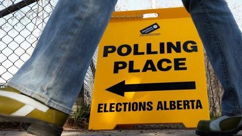 Une pancarte jaune indiquant la direction d'un bureau de vote est posée sur un trottoir. On aperçoit les jambes d'un passant qui se dirige vers ce lieu.