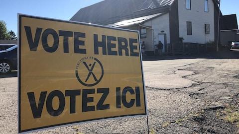 Une pancarte sur le sol sur laquelle il est écrit « VOTE HERE - VOTEZ ICI »