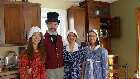 Quatre personnes, dans une cuisine, qui sont une famille. On les voit dans l'ordre suivant : une fille, le père, la mère, une fille. Ils sont habillés en habit d'époque.