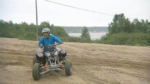 Un garçon sur un véhicule tout terrain de plage