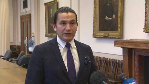 un homme porte un costume sombre et une cravate violette.