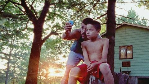 Image tirée du film  We the Animals  montrant les acteurs Raúl Castillo et Evan Rosado se tenant devant une maison située dans un secteur boisé.