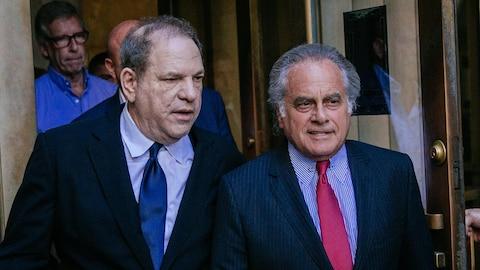 Deux hommes portant des vestons et des cravates discutent en sortant d'un bâtiment.