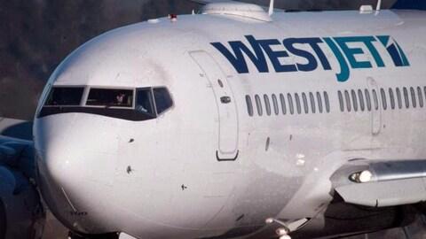 La silhouette d'un pilote vue de l'extérieur d'un appareil de Westjet.