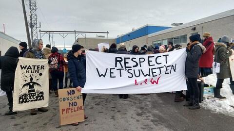 """Des manifestants tiennent un drapeau où il est écrit """"Respectez al loi Wet'suwet'en"""" et """"Pas de consentement, pas de pipeline""""."""