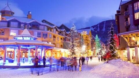 Des passants se promènent dans une rue enneigée et illuminée de Whistler à la nuit tombante.