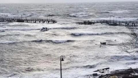 La jetée est coupée en deux formant un assez grand trou entre les deux parties. La mer est agitée et rejette plusieurs débris sur la plage.