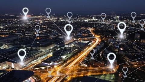 Un paysage urbain photographié de nuit sur lequel a été superposé un réseau de lignes représentant un réseau Internet.