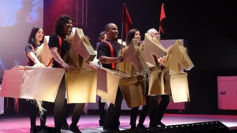 Un groupe de comédiens sont debout souriants sur scène, déguisés en cheval de carton, le costume tenant à l'aide de bretelles rouges.