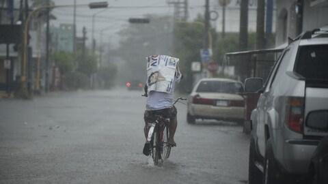 Un homme circule sur un vélo dans une rue recouverte par quelques centimètres d'eau. Le temps est lourd et il pleut.