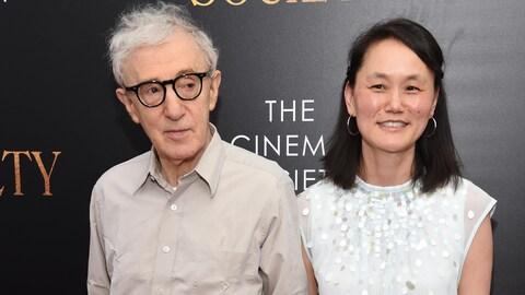 Woody Allen et Soon-Yi Previn se tiennent côte à côte. Le réalisateur regarde sur le côté, tandis que sa femme sourit aux objectifs.