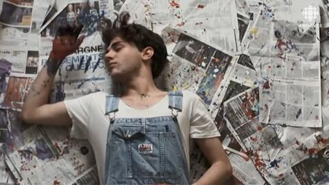 Xavier Dolan en salopette, couché sous un plancher tapissé de papier journal parsemé de peinture.