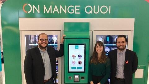 Les trois personnes à côté d'un distributeur d'aliments