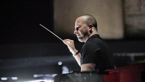 Le chef d'orchestre Yannick Nézet-Séguin tenant une baguette de direction dans une salle de répétition.