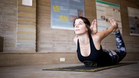 Une femme pratique une posture de yoga sur son tapis dans un studio.