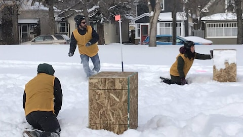 Deux joueurs de yukigassen se cachent derrière des boîtes pendant qu'un autre s'apprête à lancer une boule de neige.