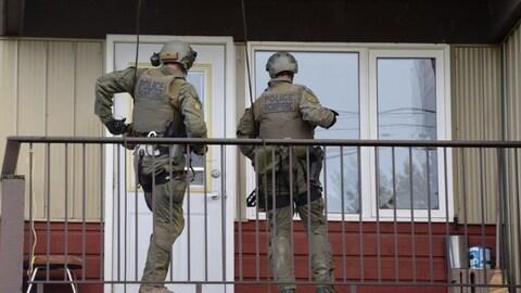Deux policiers en uniformes de combat sont sur un balcon devant la porte d'un appartement.