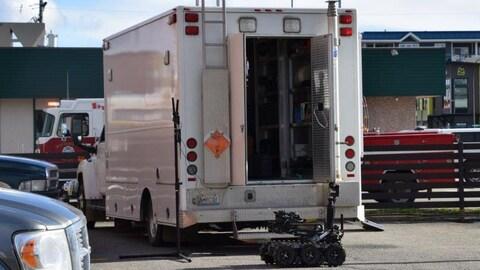 Un petit robot sur chenilles devant un grand camion dans un stationnement, avec en arrière-plan un camion de pompiers.