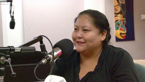 Une femme autochtone est assise derrière un micro dans un studio d'enregistrement.