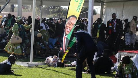 Plusieurs personnes courent dans tous les sens alors que d'autres sont couchées sur le sol après l'explosion de la bombe. Une banderole avec le visage du président Mnangagwa est au centre de la photo.