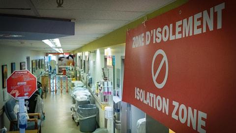 On voit en plongée un couloir d'hôpital. En gros plan, à droite de l'image, on voit un grand écriteau en rouge où il est écrit « zone d'isolement » avec le symbole d'interdiction de passer.