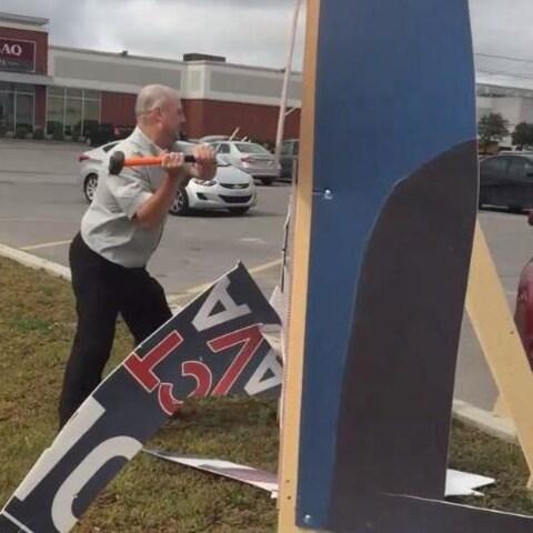 Action Laval a diffusé une vidéo où Alain Lecompte détruit le panneau de Jean-Claude Gobé et invite les citoyens à faire comme lui.