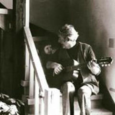 Félix Leclerc et sa fille Nathalie. Début des années 70. Félix joue de la guitare assis dans les escaliers. Nathalie assise à côté de lui, le regarde avec amour.