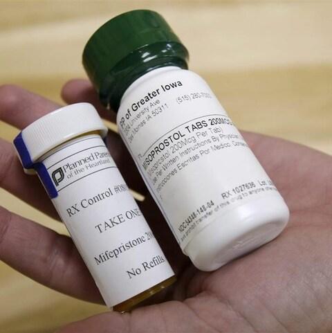 Une main contenant deux contenants de pilules abortives.