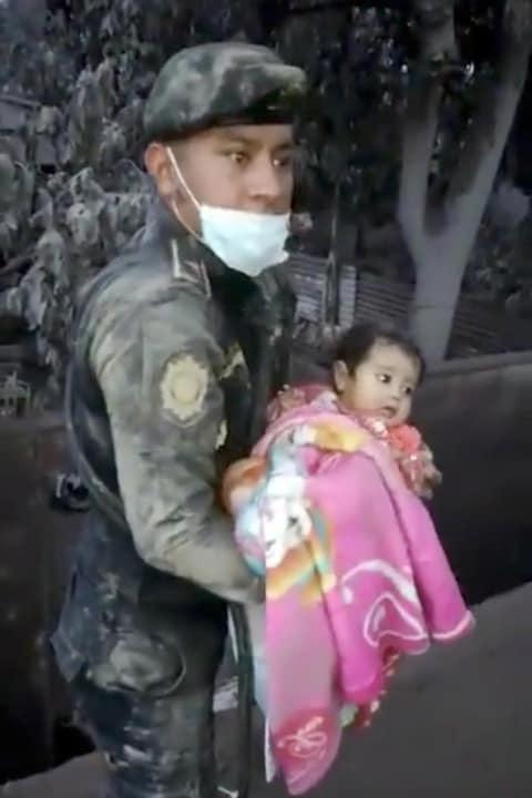 Un soldat porte dans ses bras une petite fille qu'il vient de sortir des décombres après l'éruption du volcan de Fuego, à Escuintla, au Guatemala.
