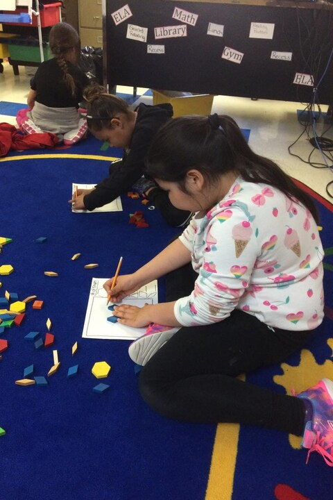 Des enfants dessinent sur un tapis bleu dans leur classe.