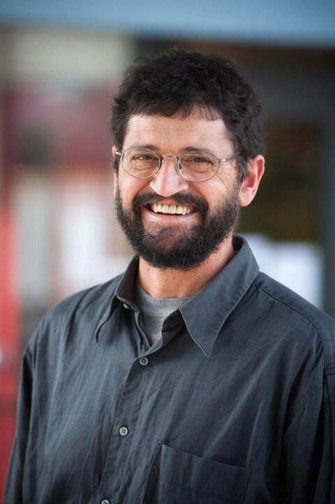 Portrait de Gary Hinshaw souriant et portant des lunettes et une barbe noire.