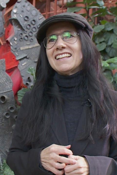 Josée Thibeault devant une sculpture dans la cour de La Cité francophone à Edmonton.