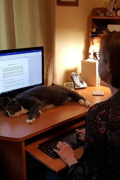 Martine Noël-Maw dans son bureau à domicile écrit à l'ordinateur. Devant le moniteur, un chat gros et blanc est étendu sur la table.
