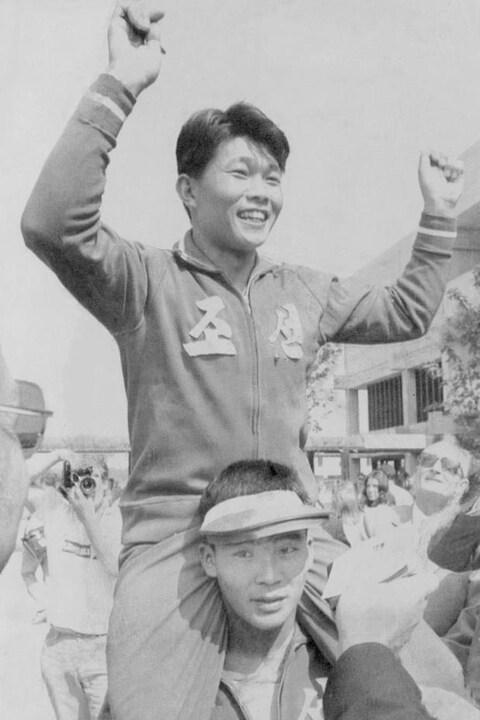 Ri Ho-jun célèbre sa victoire soulevé par un camarade.