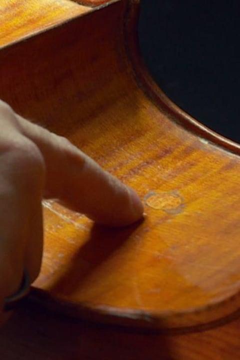 La main d'un homme pointe vers une marque ronde dans le bois, sur le flanc d'un violoncelle.