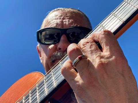 Le musicien André Thibault avec sa guitare.