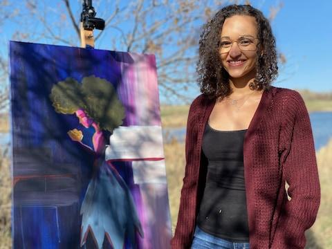 L'artiste visuelle Diana Ntibandetse est debout devant son tableau dans un parc de Regina. C'est un tableau d'une femme qui tient des objets dorés dans les mains.