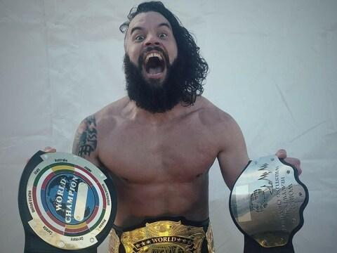 Markus Burke tenant ses trois ceintures de champion