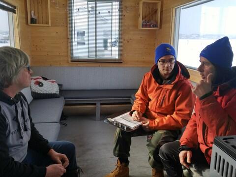Deux membres du club TERRE procèdent à l'évaluation des besoins en énergie d'une cabane à pêche.