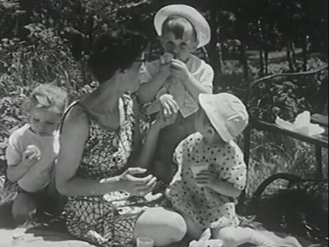 Mère accroupie sur une nappe de pique-nique, entourée de trois enfants qui mangent des fruits.