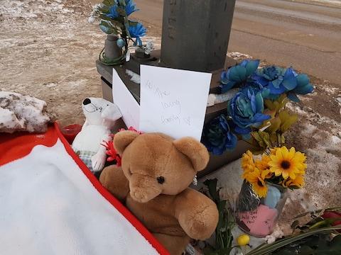 Des fleurs, des jouets et des mots de soutien se trouvent à la base d'un poteau.