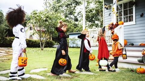 Cinq enfants vêtus de costumes d'Halloween attendent patiemment leur tour pour recevoir des bonbons devant le porche d'une maison.