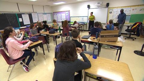 Une douzaine d'élèves sont assis à leur pupitre et discute avec une femme à l,avant de la classe.